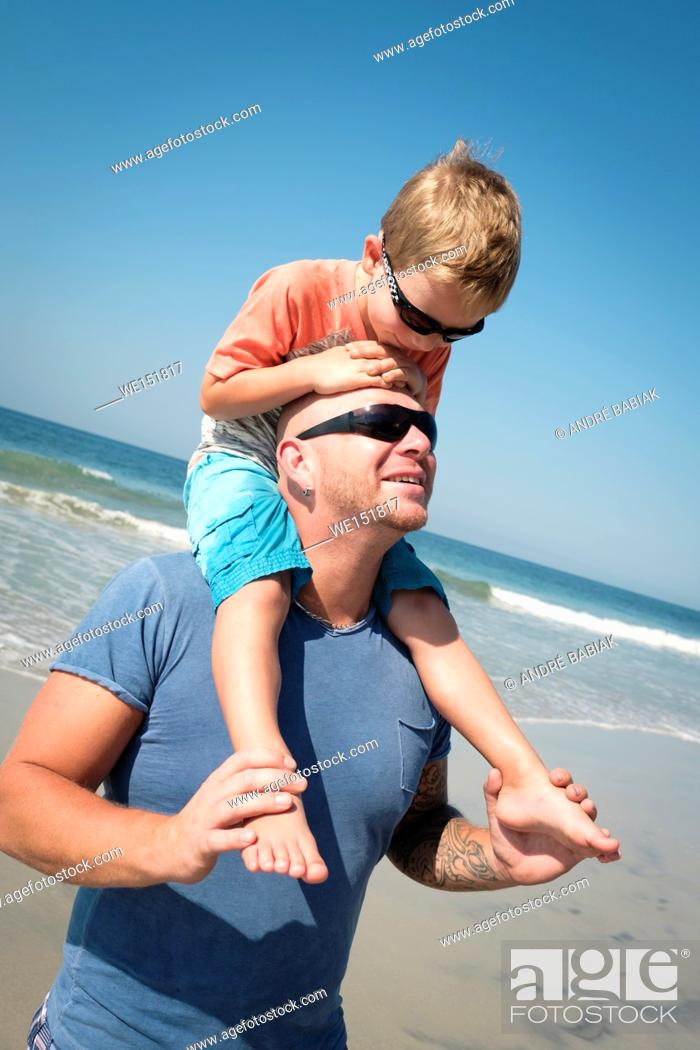 Stock Photo: Caucasian father carrying his 4 years old son on his shoulders.