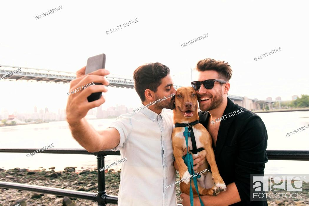 Stock Photo: Young male couple on riverside taking smartphone selfie with dog, Astoria, New York, USA.
