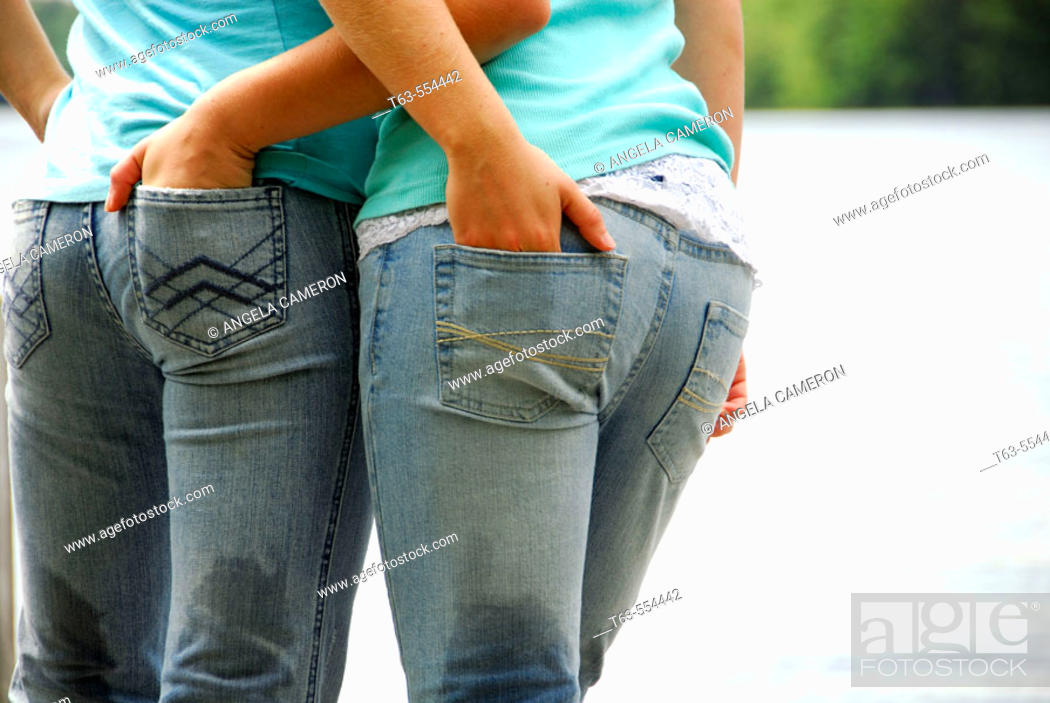 Stock Photo: girl 13 girl 18 standing together with hands in each others jean pockets.