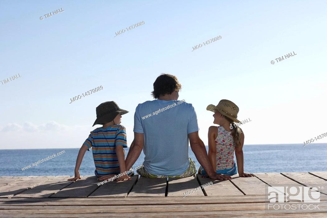Stock Photo: Father and two children 7-9 sitting on jetty back view.