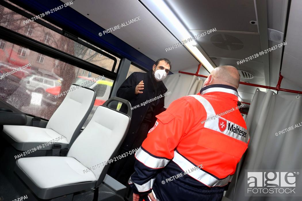 Stock Photo: 28 January 2021, Bavaria, Memmingen: Klaus Holetschek (CSU), Bavarian Minister of Health, stands in a vaccination bus with an employee of the aid organisation.
