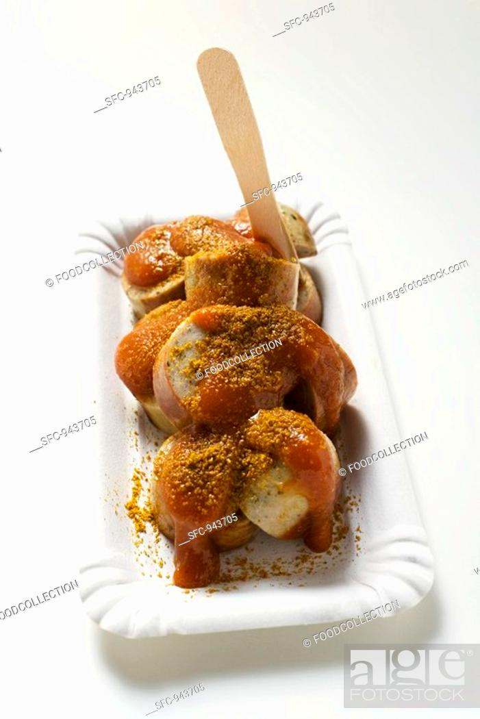Stock Photo: A currywurst sausage with ketchup & curry powder with wooden fork.