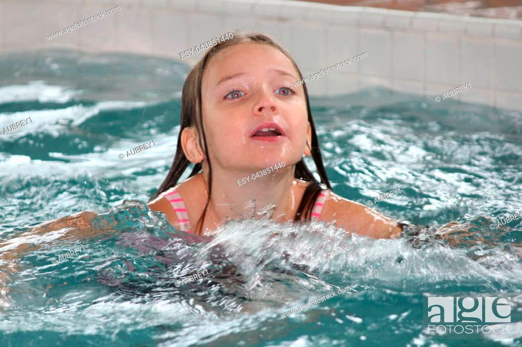 Stock Photo: Girl child frolicking in the shallow end of a swimming pool.