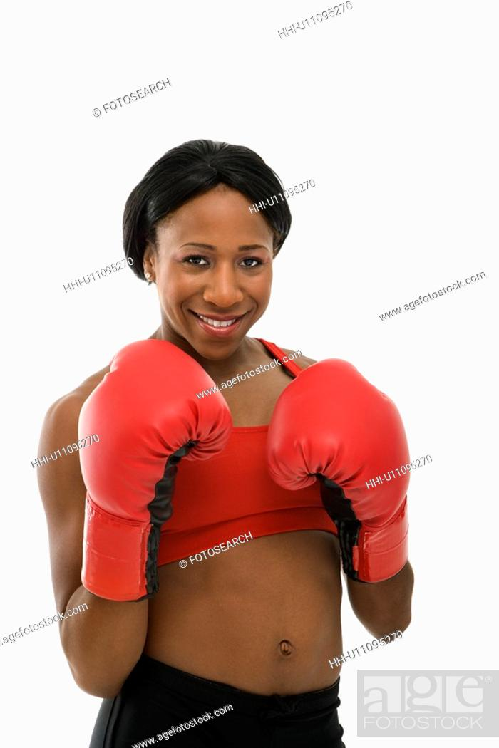 Stock Photo: African American young adult woman wearing boxing goves smiling at viewer.