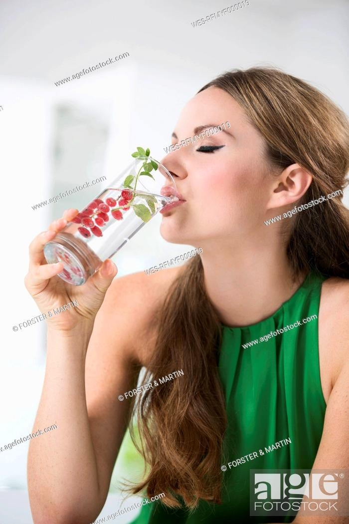 Stock Photo: Germany, Young woman drinking water from glass with berries.