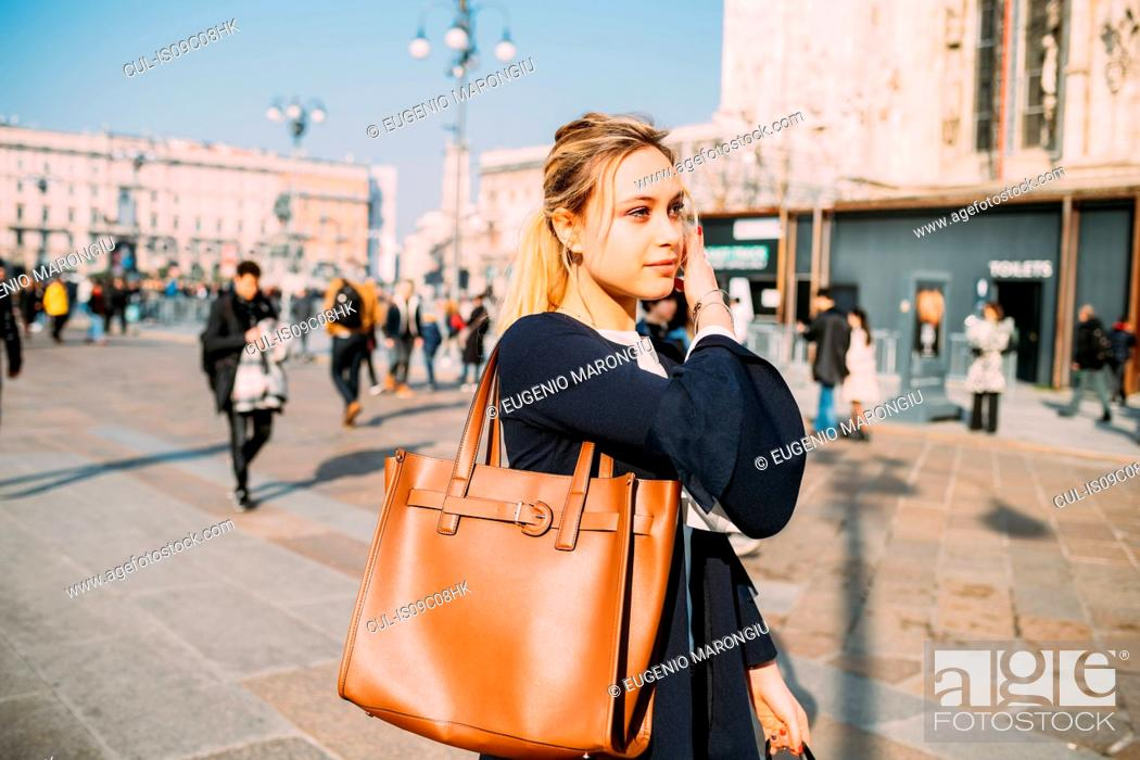 Stock Photo: Young female tourist strolling and listening to earphones in city square, Milan, Italy.
