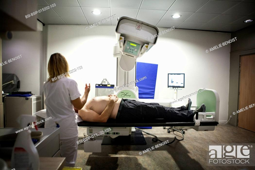 Stock Photo: Reportage in a radiology centre in Haute-Savoie, France. A technician prepares a patient for an arthography of the shoulder.