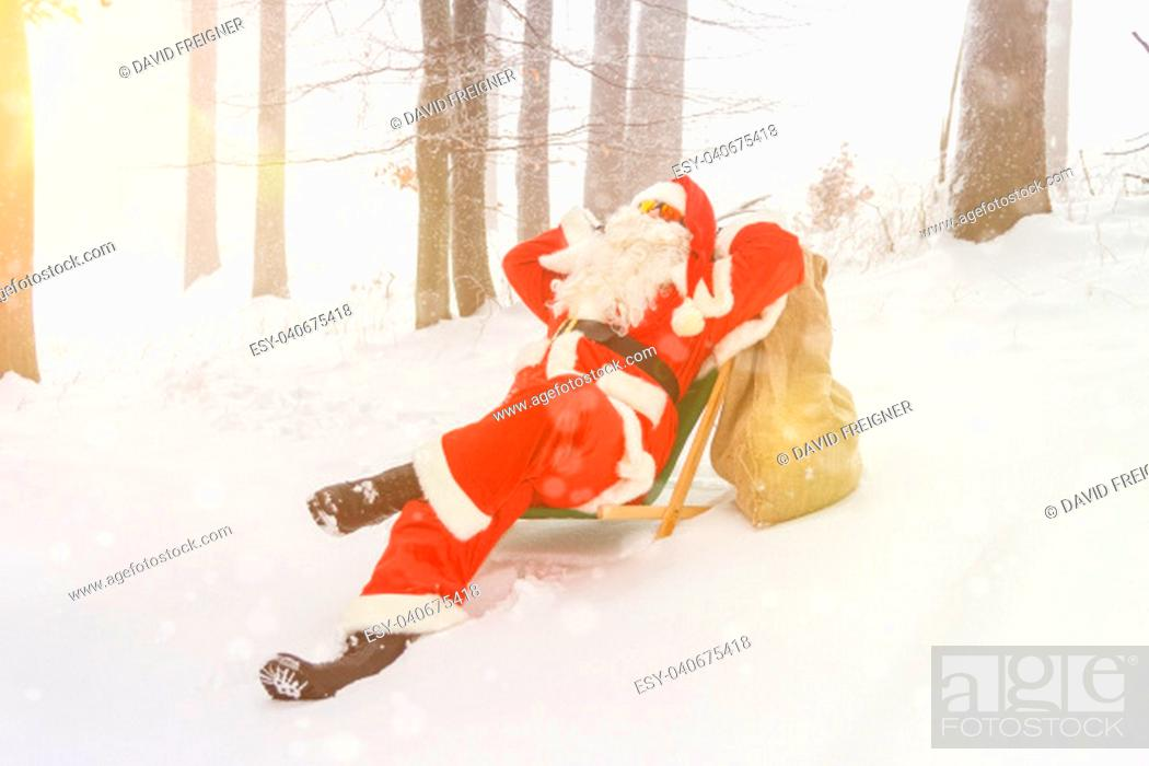 Stock Photo: Santa Claus relaxing in a lounger in the woods.