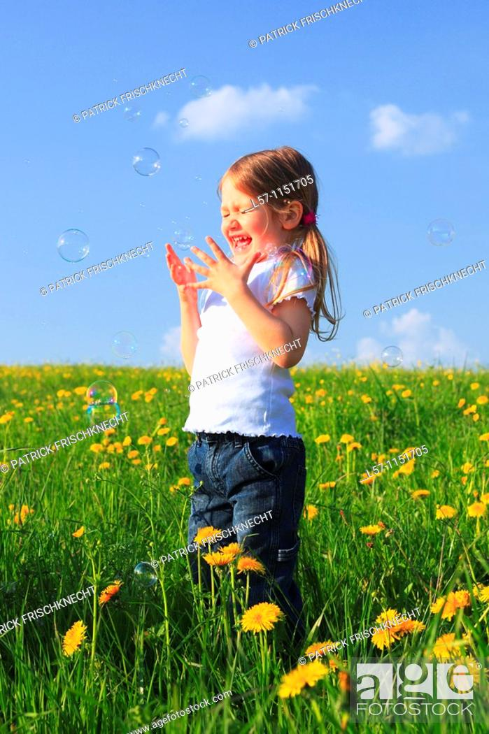 Stock Photo: girl playing with bubbles in field of Dandelions, Zuercher Oberland, Zuerich, Switzerland.