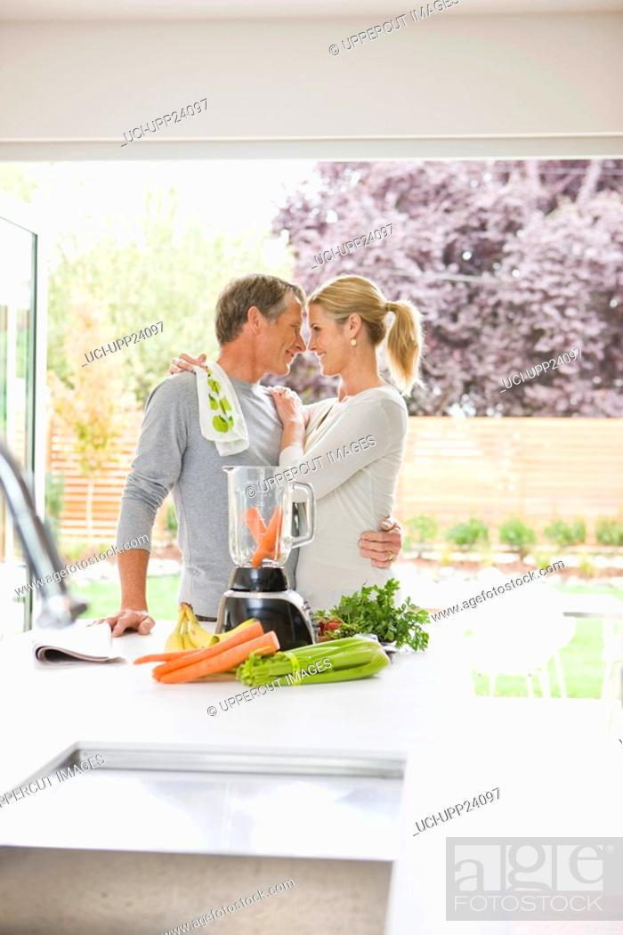 Stock Photo: Hugging couple preparing health shake in kitchen.