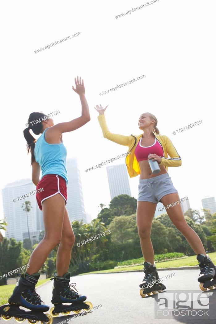 Stock Photo: Women on rollerblades high fiving.