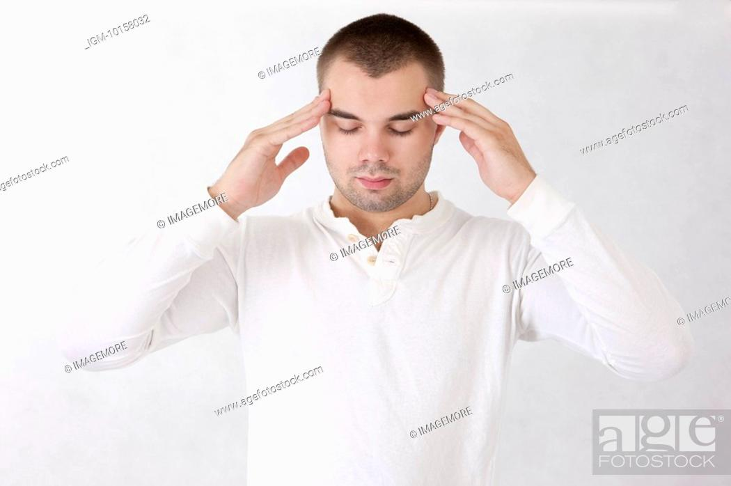 Stock Photo: Young man putting hands on head and thinking with eyes closed.