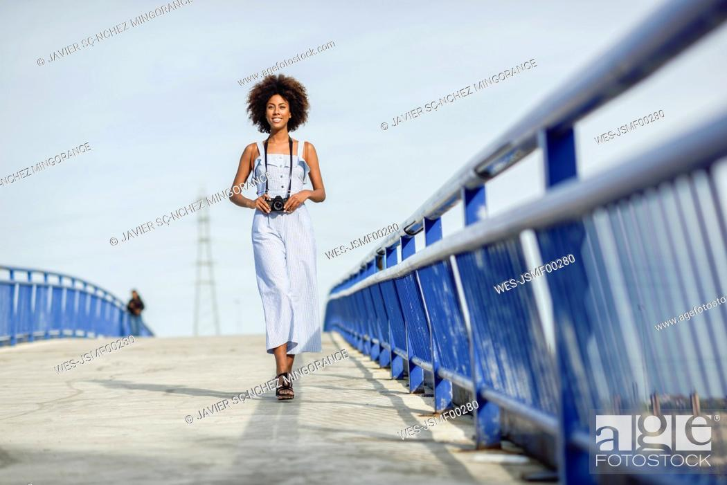 Stock Photo: Content young woman with camera walking on a bridge.