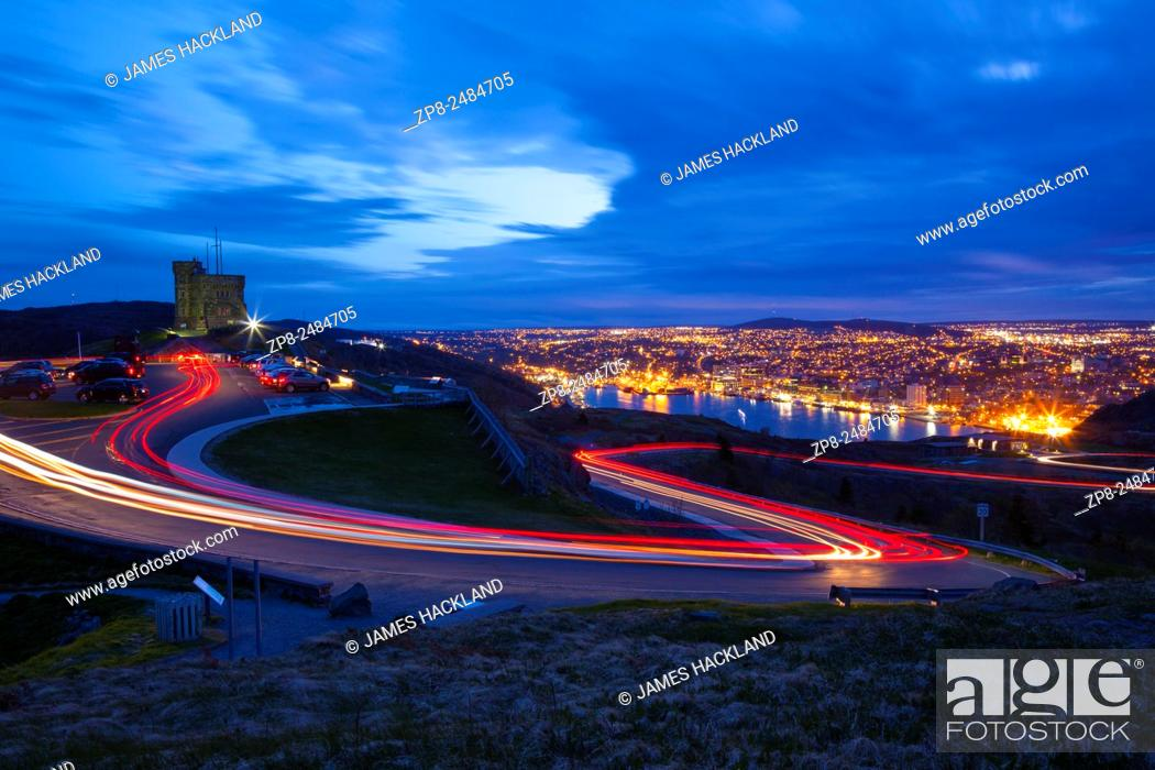 Stock Photo: Light trails created by cars as they zip up and down Signal Hill with St. John's and its harbour in the background at dusk. Newfoundland, Canada.
