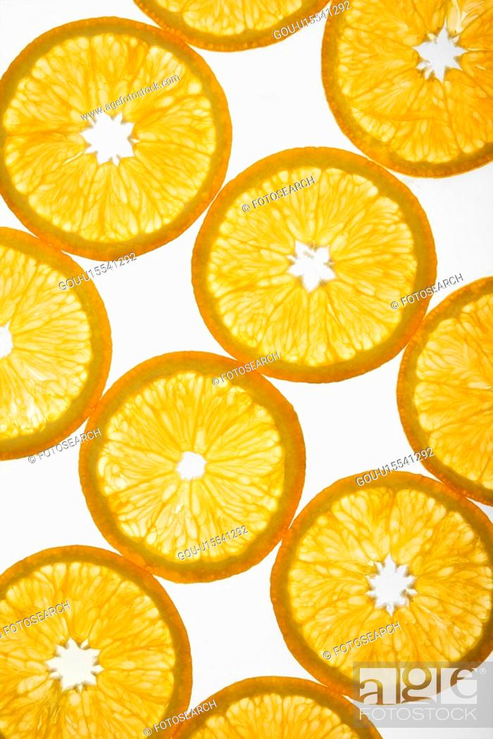 Stock Photo: Orange slices arranged in design on white background.