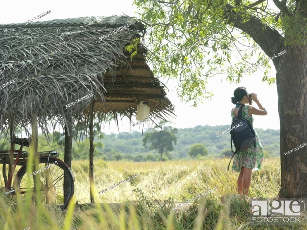 Stock Photo: Young woman looking through binoculars bicycle under thatched roof.