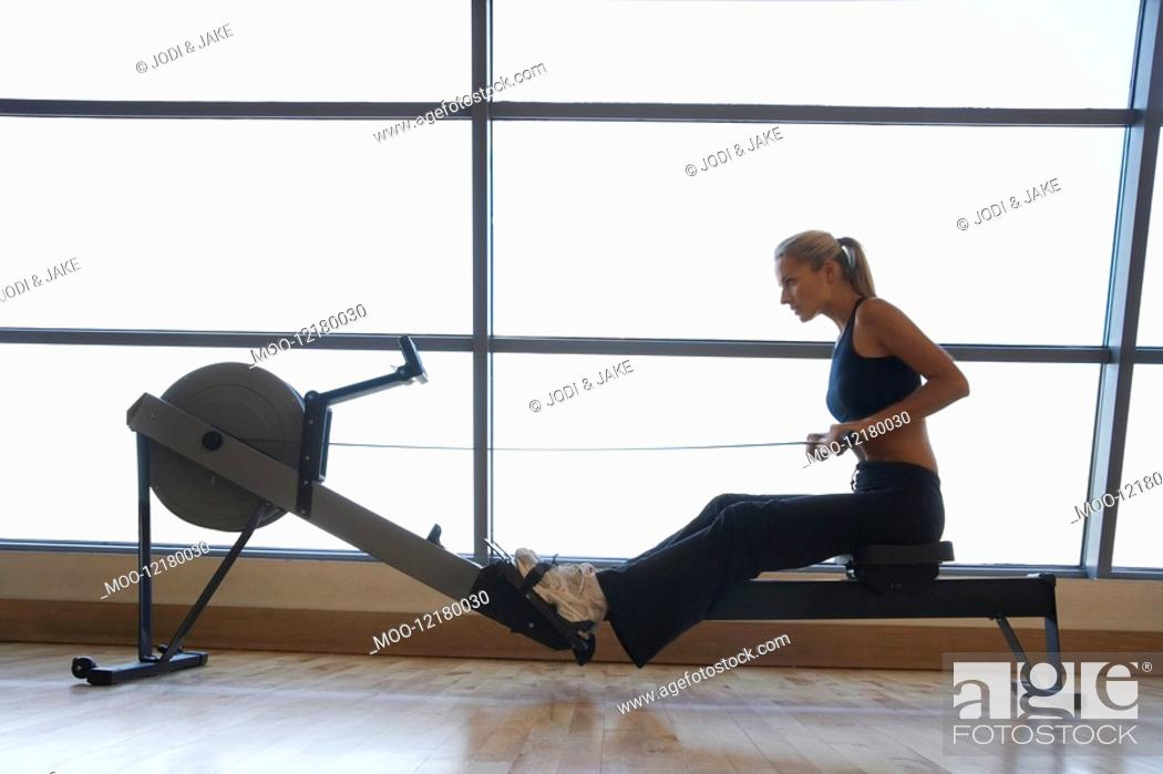 Stock Photo: Women Using Rowing Machine in health club side view.