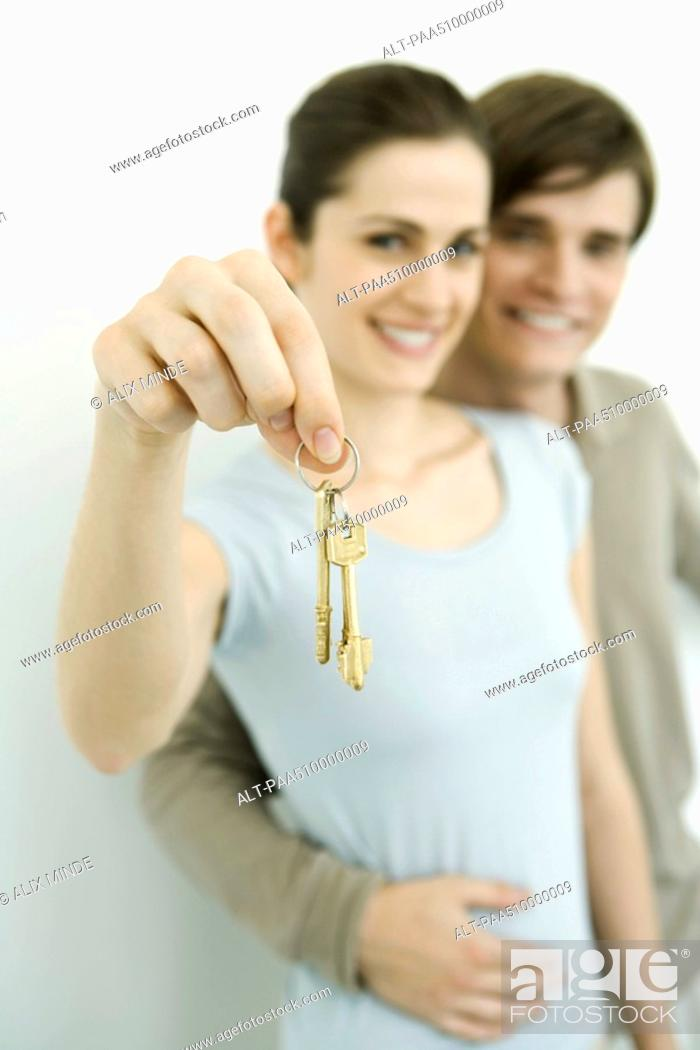 Stock Photo: Young couple smiling at camera, woman holding up set of keys.