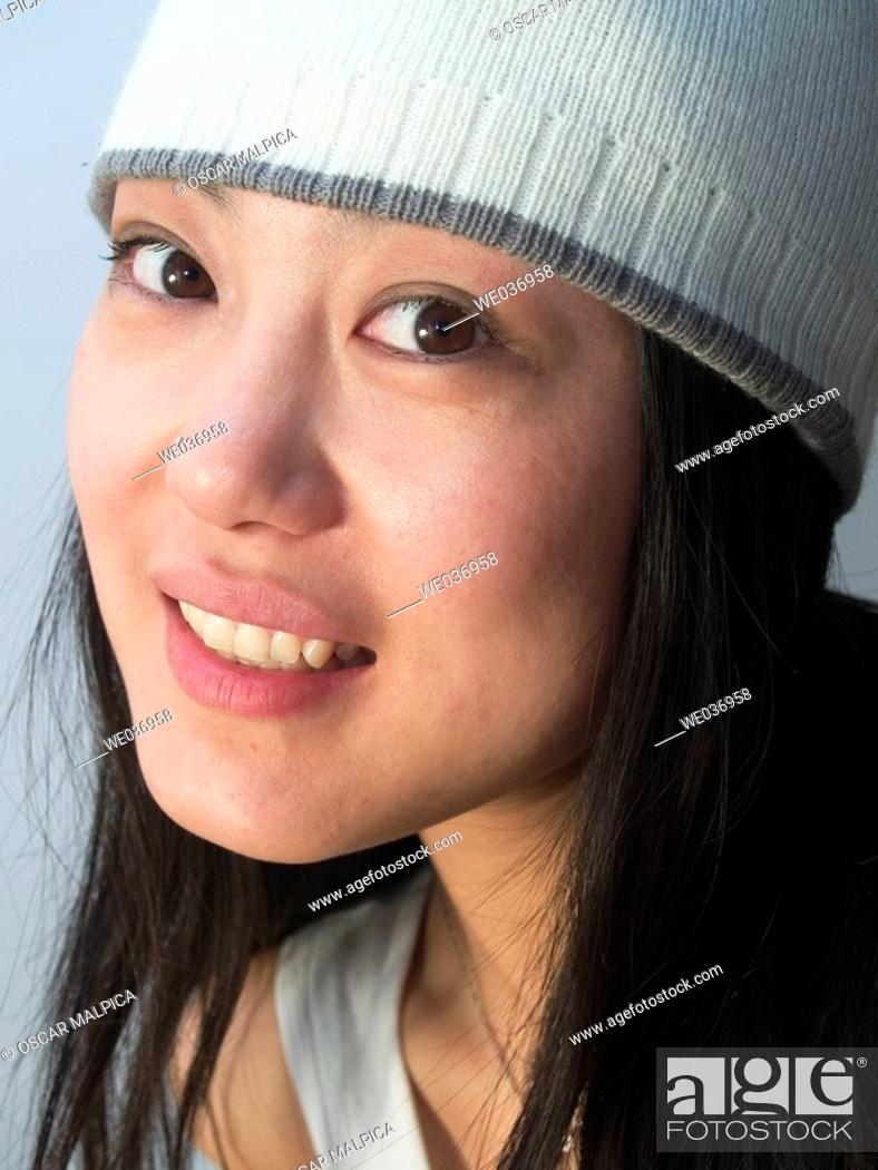 Stock Photo - young good looking asian girl wearing a winter hat.