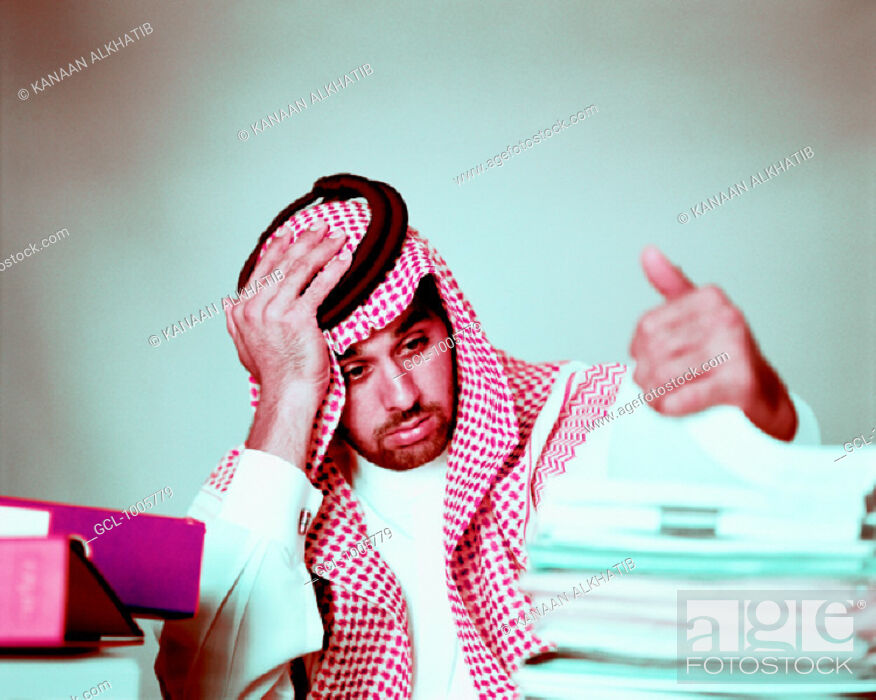 Stock Photo: Overworked Arab businessman with piles of folders.