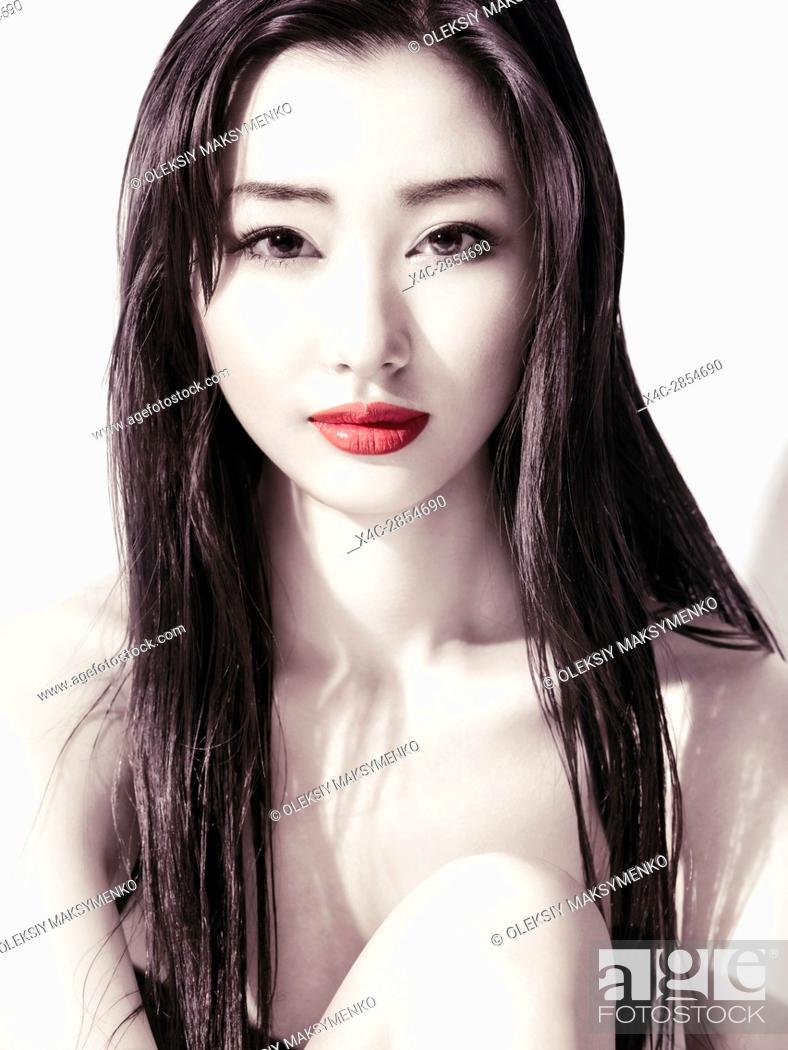 Photo de stock: Sensual artistic beauty portrait of a young asian woman beautiful face with long dark hair, faided colors, green eyes and red lips.