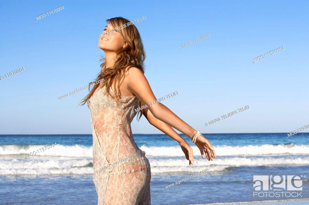 Stock Photo: Young woman in summer dress posing by sea.