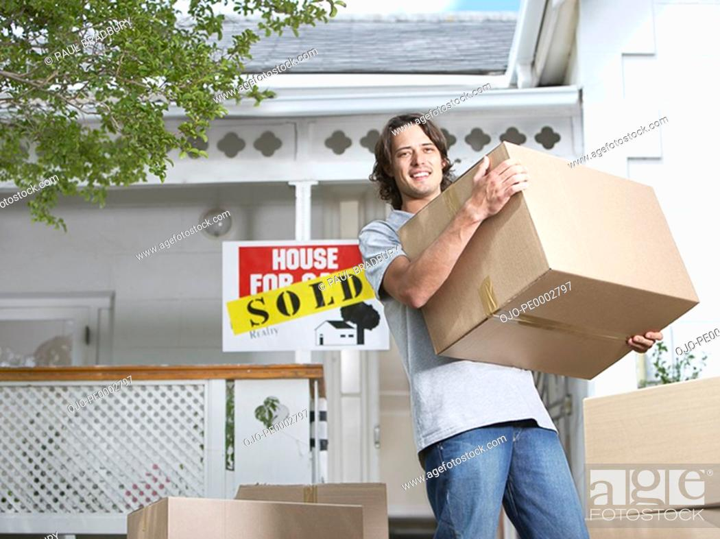 Stock Photo: Man with cardboard boxes standing in front of house with sold sign.