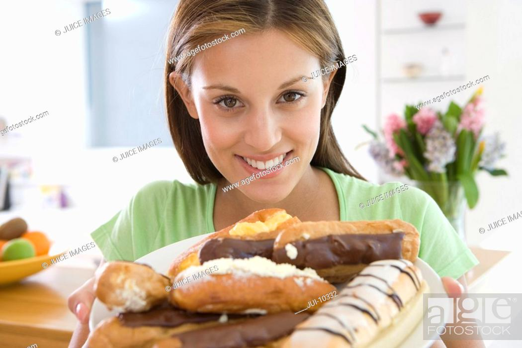 Stock Photo: Young woman with plate of pastries, smiling, portrait, close-up.