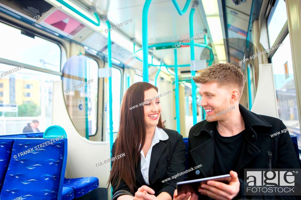 Imagen: Businesswoman and businessman using digital tablet in Docklands Light Railway train, London.