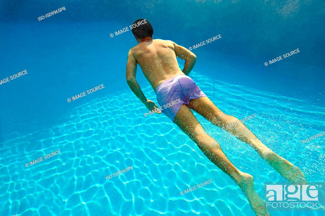 Stock Photo: Young man swimming underwater in swimming pool.