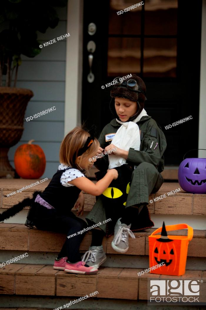 Stock Photo: Boy and sister trick or treating in cat and pilot costume sitting on stairway looking in bags.