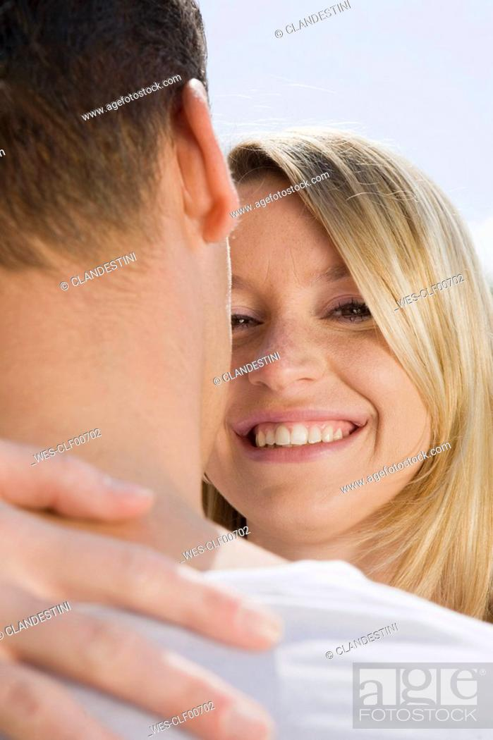 Stock Photo: Germany, Bavaria, Munich, Young couple embracing, smiling, portrait, close-up.