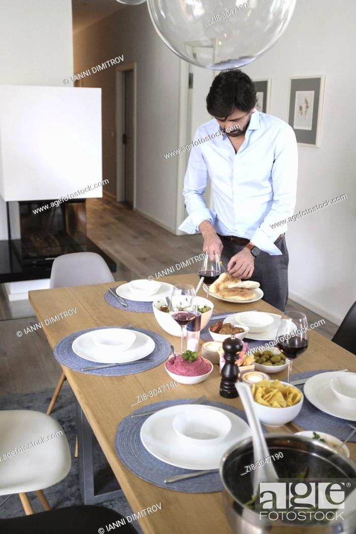 Stock Photo: Man setting dinnertable with vegetarian food.