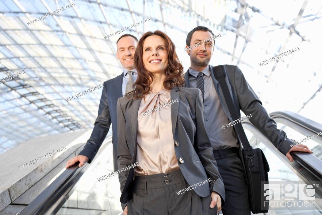 Stock Photo: Germany, Leipzig, Business people on escalator, smiling.