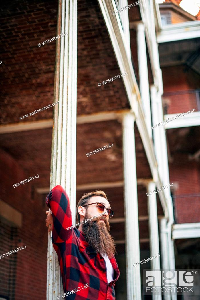 Stock Photo: Man with beard leaning against a pillar.