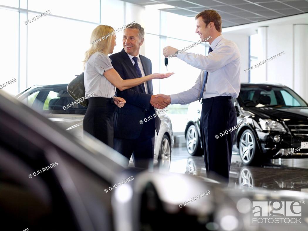 Stock Photo: Salesman handing couple keys to new car in showroom.