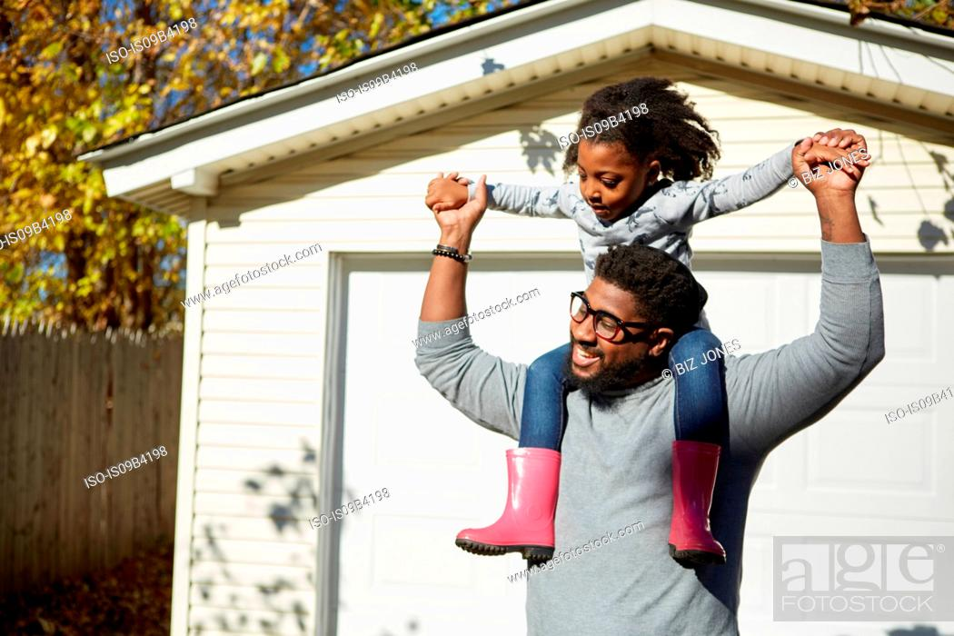 Stock Photo: Mature man carrying daughter on shoulders by residential garage.
