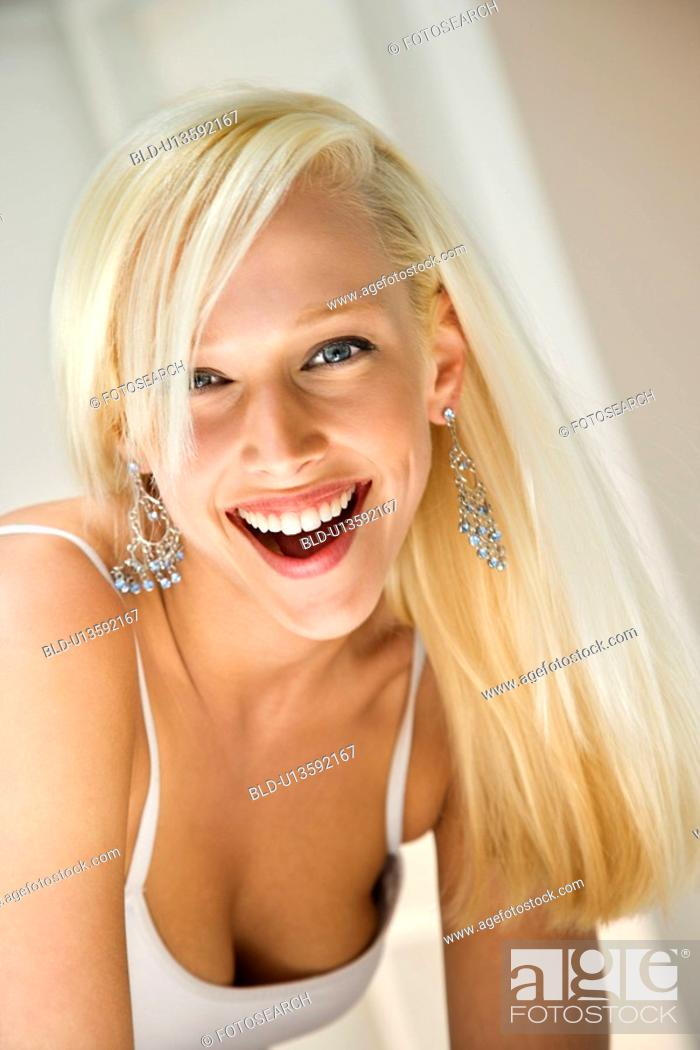 Stock Photo: Portrait of attractive blonde young adult woman smiling and looking at viewer.