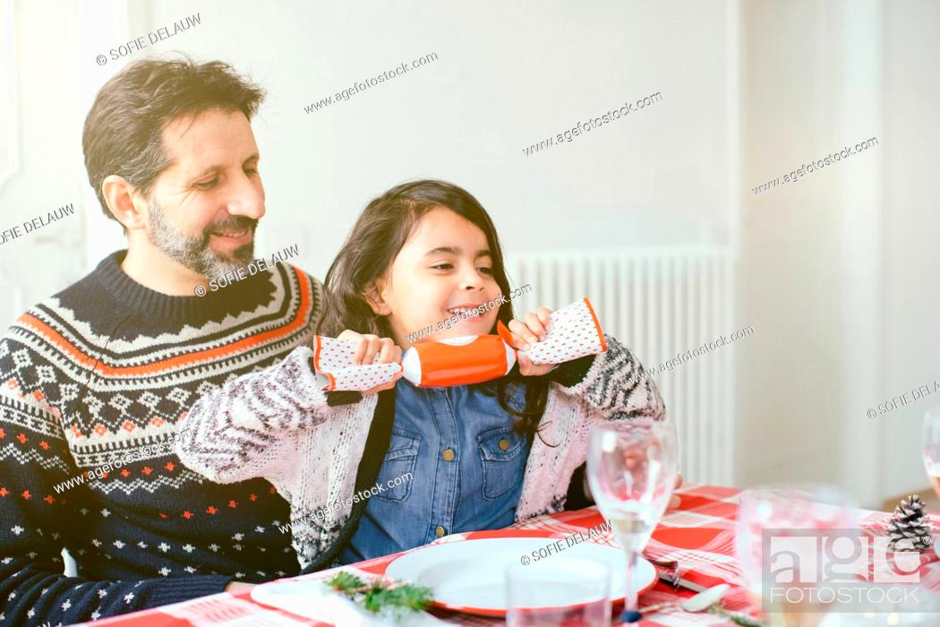 Stock Photo: Girl with Christmas cracker at family Christmas party.