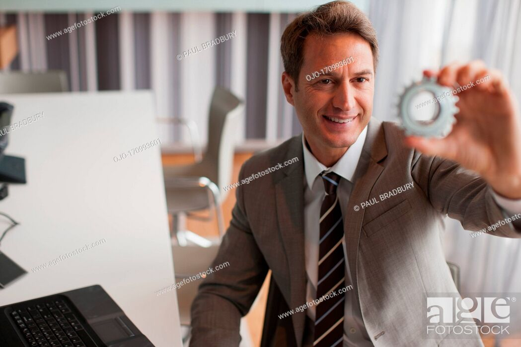 Stock Photo: Businessman looking at cog.