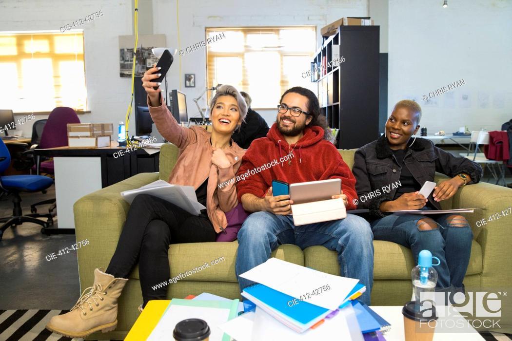Stock Photo: Happy creative business people taking selfie in casual open plan office.
