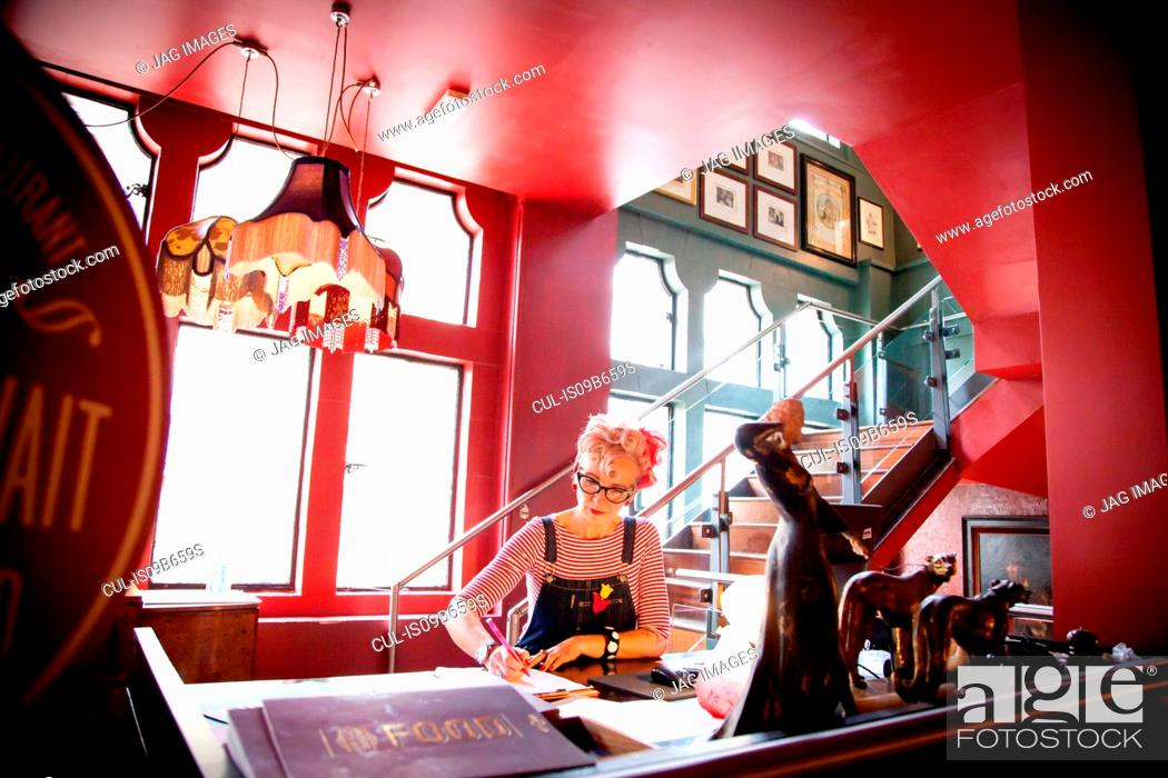 Stock Photo: Quirky woman working at high counter at bar and restaurant, Bournemouth, England.