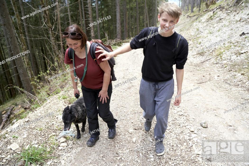 Stock Photo: Mature woman and teenager walking on a path in the forest, with dog. Bad Tölz, Upper bavaria, Germany.
