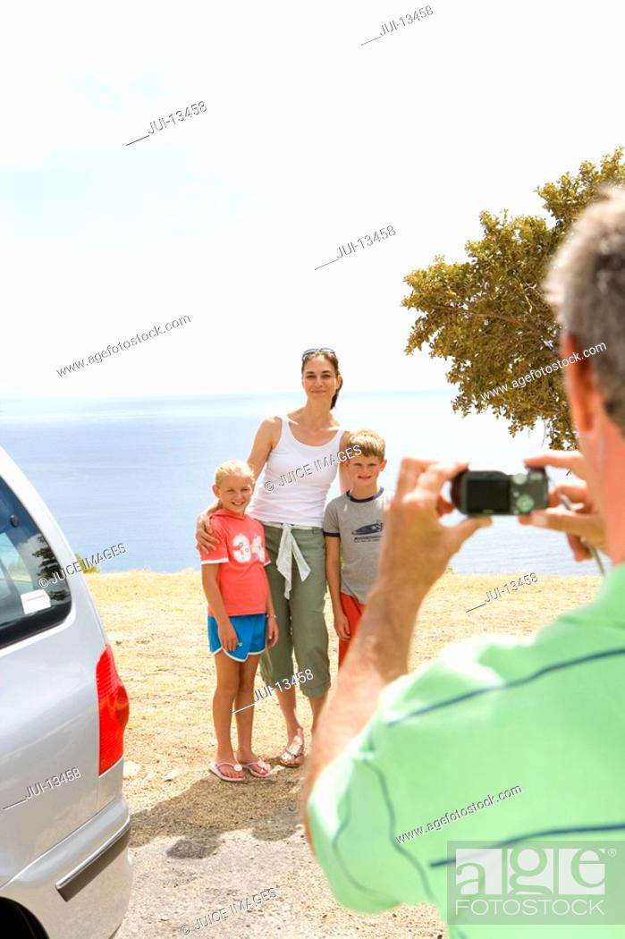Stock Photo: Father taking photograph of mother with son and daughter 6-10 on beach, smiling.