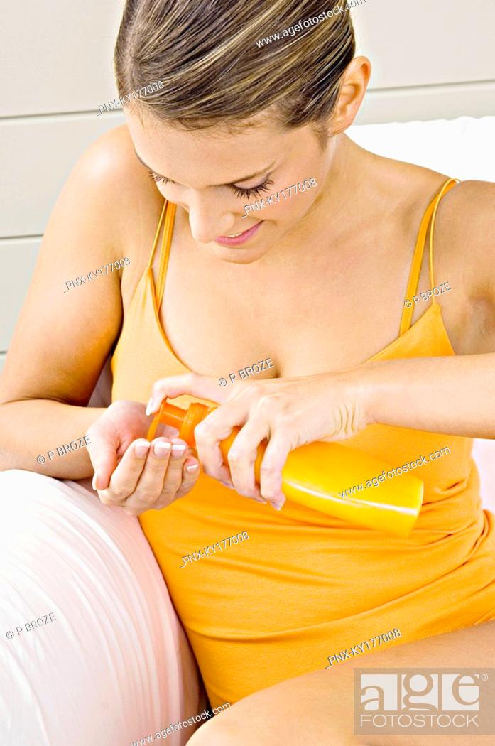 Stock Photo: Close-up of a young woman squeezing moisturizer from a bottle.