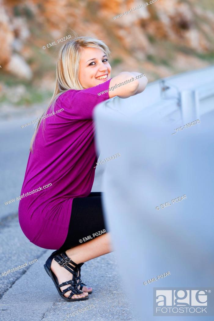 Stock Photo: Attractive young woman happy smiling smile squatting by the road.