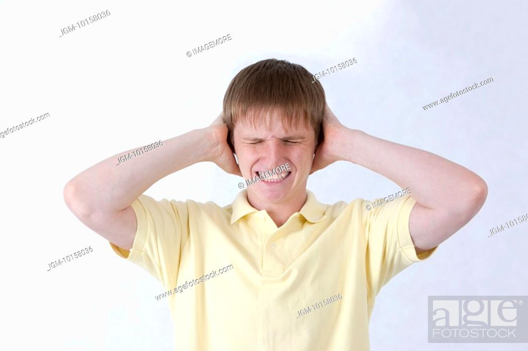 Stock Photo: Young man frowning with eyes closed and head in hands.