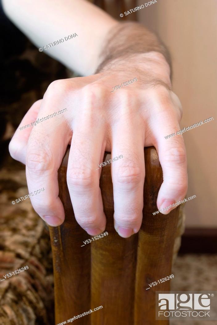 Stock Photo: Hand grabbing armchair.