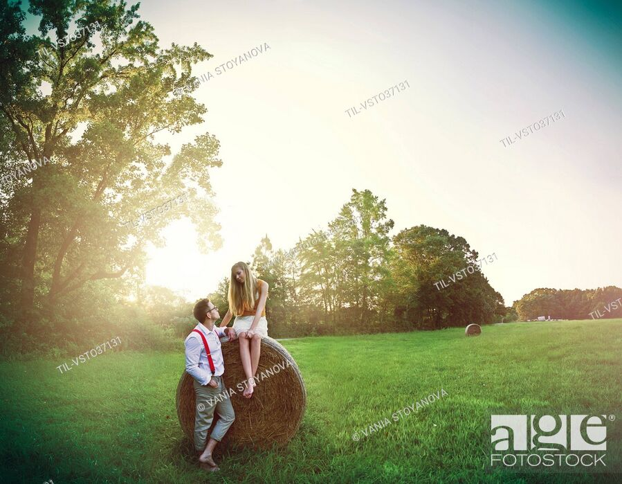 Imagen: young couple in a field, girl sitting on a hay bail as young man wearing red braces flirts looking at young woman.