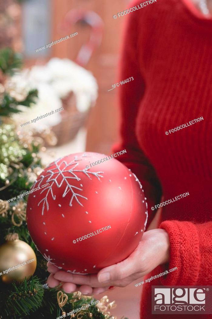 Stock Photo: Woman holding large red Christmas bauble.